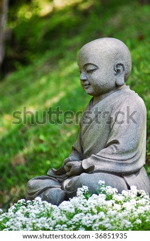 Little Buddha statue in the garden flowers