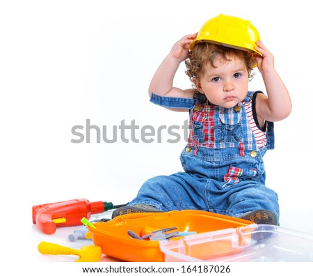 Little builder. Baby boy in a helmet plays in the builder with tools. Isolated over white.