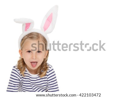Little bunny. Portrait of an attractive little child wearing bunny ears looking to the camera showing her tongue at the studio isolated on white. - stock photo