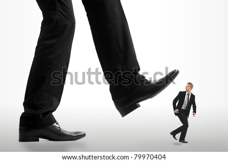 Little business man being crushed by the feet of a giant business man - stock photo
