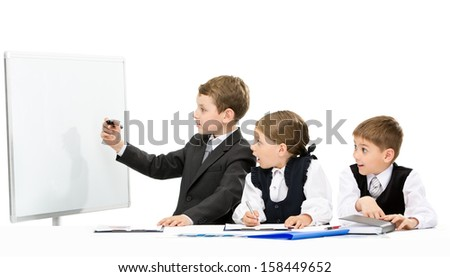 Little business man showing something on screen to the group of little business people, isolated on white. Concept of teamwork and cooperation