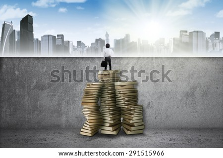 Little businessman holding a suitcase and standing on the books to see the city - stock photo