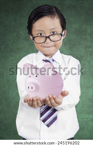 Little businessman showing piggybank, shot in class - stock photo