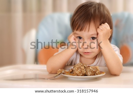 Little Caucasian baby eats at the table - stock photo