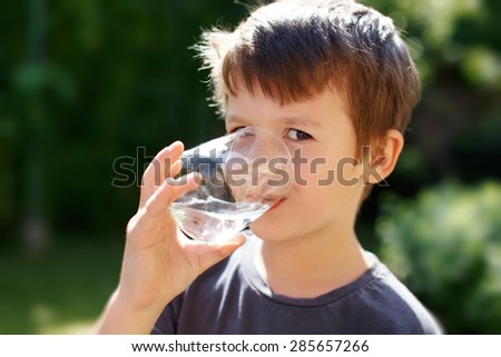 Little caucasian boy drink water in nature - stock photo