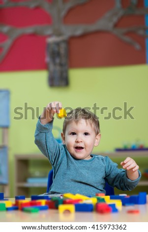 Little caucasian boy playing with Montessori toy in pre-school - stock photo