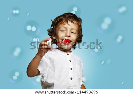 little caucasian boy with soap bubbles on blue background - stock photo