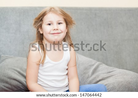 Little Caucasian girl with disheveled hair sitting on the couch with a sly grin - stock photo