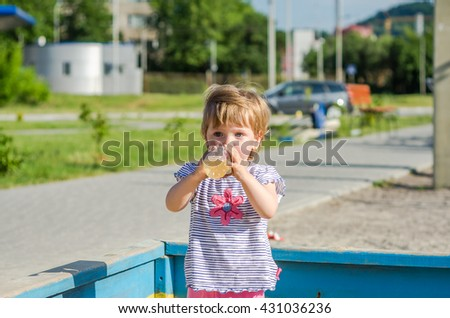 Little charming girl baby playing on the playground, drinks water from a plastic bottle