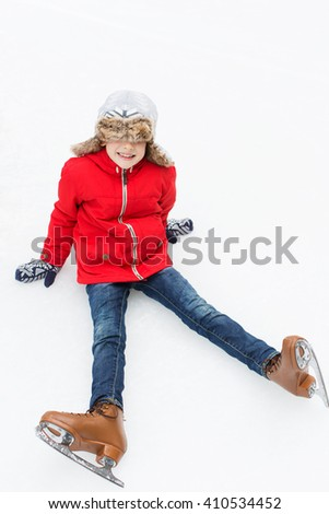 little cheerful boy being silly and enjoying winter fun activities or ice skating at winter vacation or break - stock photo