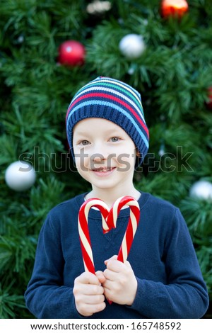 little cheerful boy making a heart shape from candy canes at christmas time - stock photo