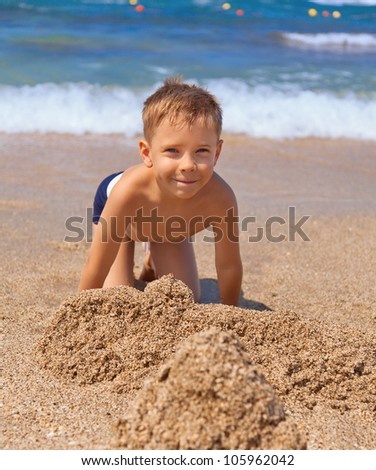 little cheerful boy on the beach with sand - stock photo