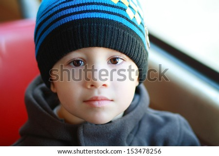 Little cheerful child boy sitting in the city train