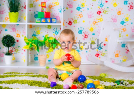 little cheerful child plays with a ball in the nursery, fun game very happy - stock photo