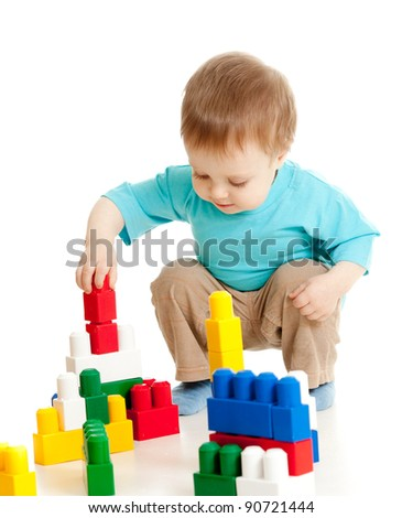 little cheerful child with construction set over white background - stock photo