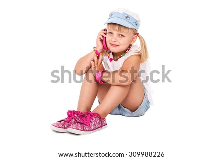 Little cheerful girl in bright clothes talking on a cell phone on a white background isolated.