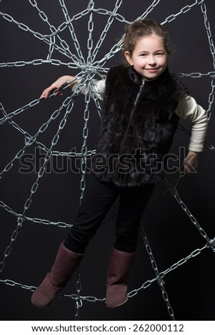 Little cheerful girl posing on the web of chains - stock photo