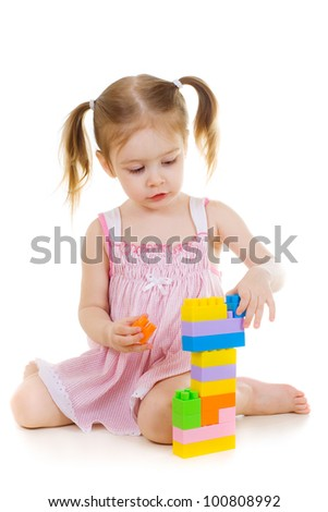 little cheerful girl with construction set over white background - stock photo