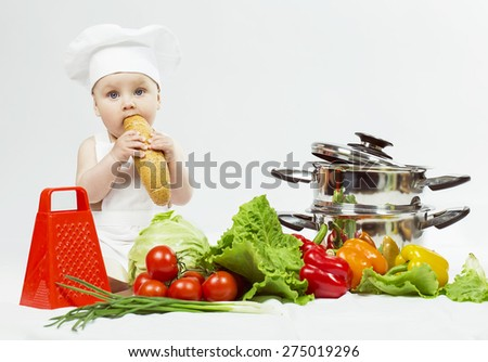 Little Chef boy preparing healthy food and eating a loaf of bread over white background. the concept of vegetarianism - stock photo