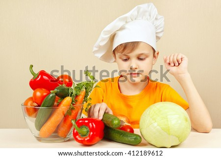 Little chef chooses vegetables for salad at the table - stock photo