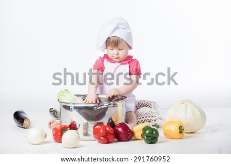 Little chef girl preparing healthy food on white background