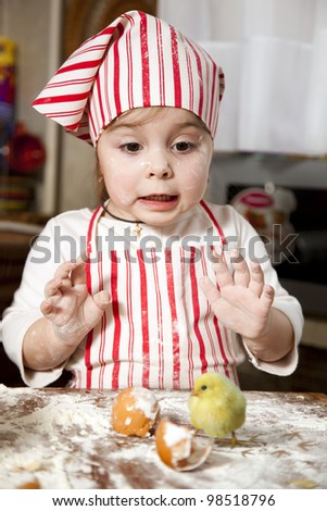 little chef in the kitchen ,wearing an apron and headscarf,surprise looking at hatched chick