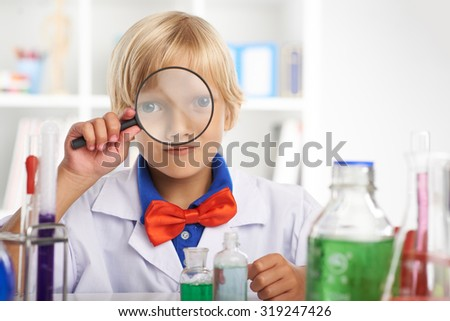 Little chemist looking at camera through magnifying glass