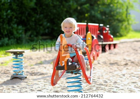 Little child, adorable blonde toddler girl, enjoying warm sunny summer or autumn day at the playground bouncing on spring horse - stock photo