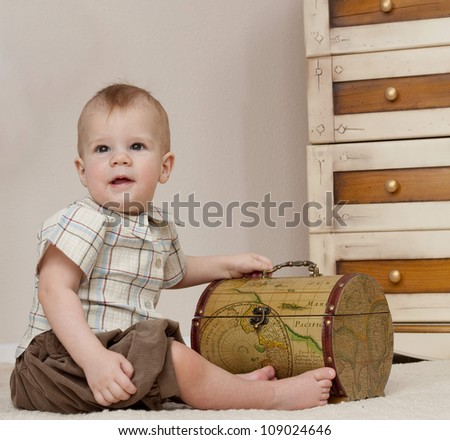 little child baby boy sitting on the floor indoors in baby room - stock photo