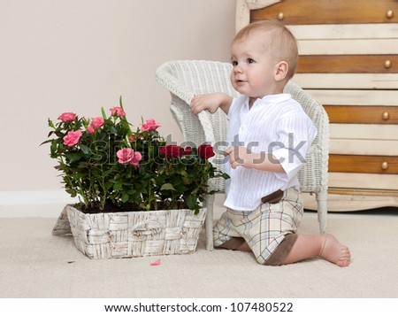 little child baby boy sitting on the floor indoors in baby room with flowers roses - stock photo