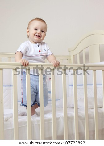 little child baby boy standing in bed  indoors in baby room smiling happy