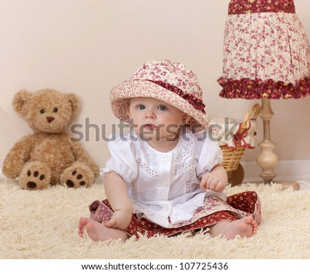 little child baby girl sitting on floor indoors in baby room teddy bear hat dress