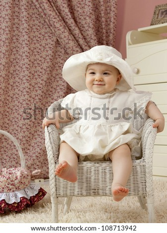 little child baby girl sitting on the chair indoors in baby room smiling