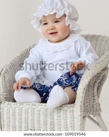 little child baby girl sitting on the chair indoors studio shot smiling fashion clothing