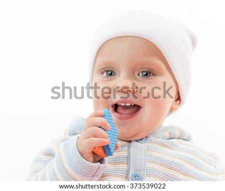 little child baby smiling boy portrait face toothy smile happy cheerful warm clothing hat blue isolated on white studio shot