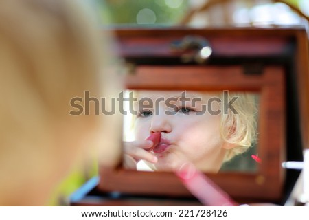 Little child, beautiful toddler girl with blonde curly hair, applying mom's pink lipstick to her lips looking at the mirror