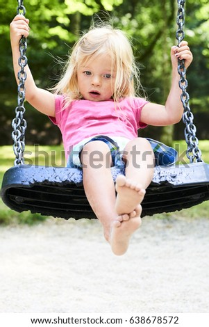 Little child blond girl having fun on a swing outdoor. Summer playground.