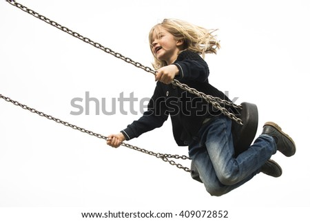 Little child blond girl having fun on a swing outdoor. Summer playground. Girl swinging high  - stock photo