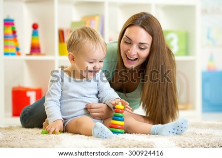 little child boy and his mommy play with toys at home - stock photo