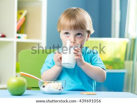 Little child boy holding glass of milk - stock photo