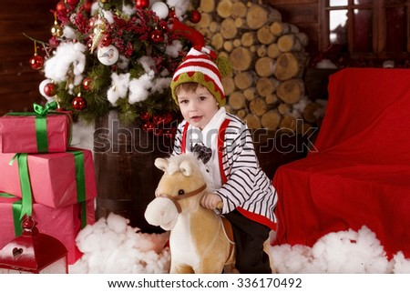 Little child (boy) in festive attire sits on toy horse near the Christmas tree with Christmas decorations and gifts  - stock photo