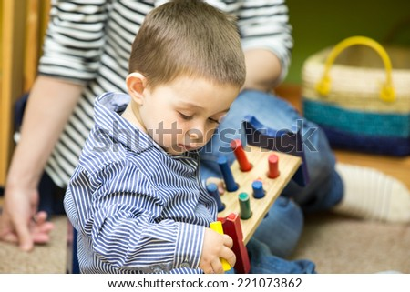 Little child boy playing in kindergarten in Montessori preschool Class. - stock photo