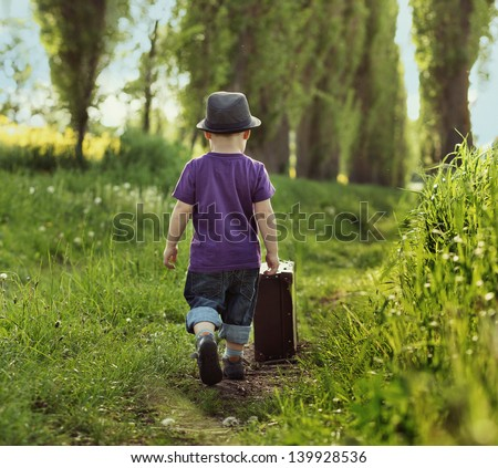 Little child carrying a suitcase - stock photo