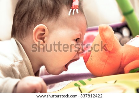 little child crying on toy cat showing his courage and superiority - stock photo