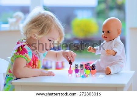 Little child, cute toddler girl having fun playing at home with colorful nail polish doing manicure and painting nails to her doll - stock photo