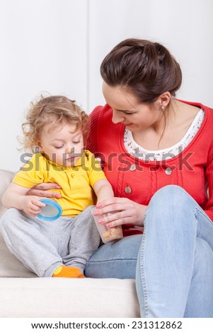 Little child eating snacks with mother, vertical