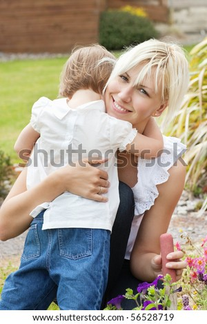 Little child embrace her mother in the garden - stock photo