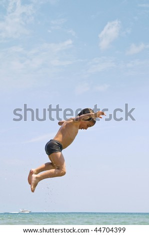 """Little child """"flying"""" in the beach - stock photo"""