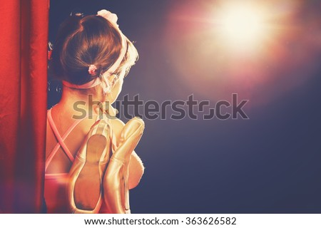 little child girl ballerina ballet dancer on the stage in red side scenes and looking in odeum - stock photo