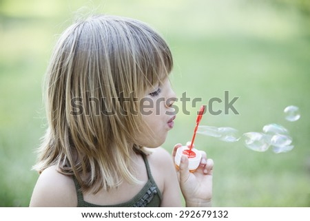 Little child girl blowing soap bubbles outdoor. Happy carefree childhood - stock photo